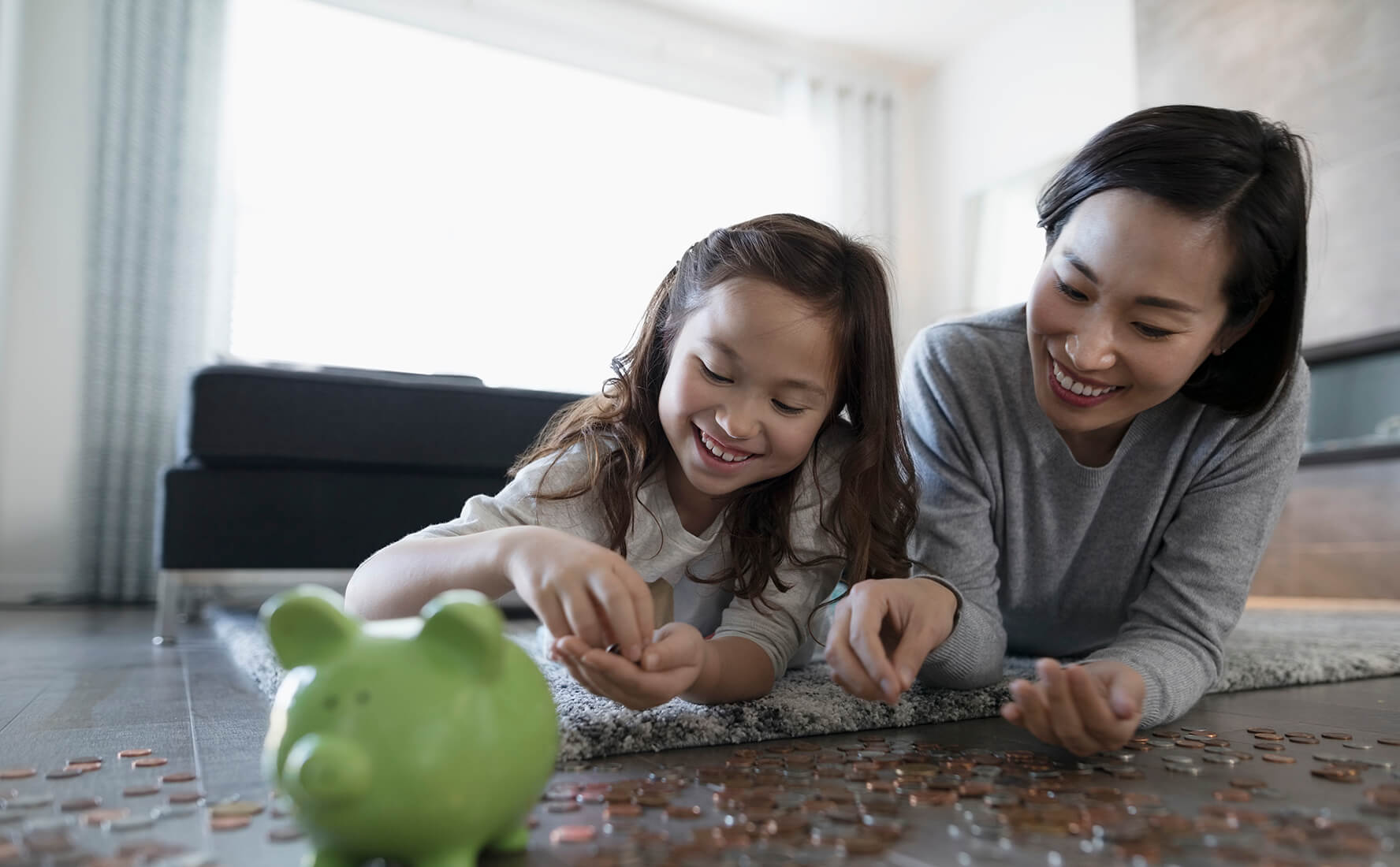 Kids savings accounts, mom and daughter learning to bank