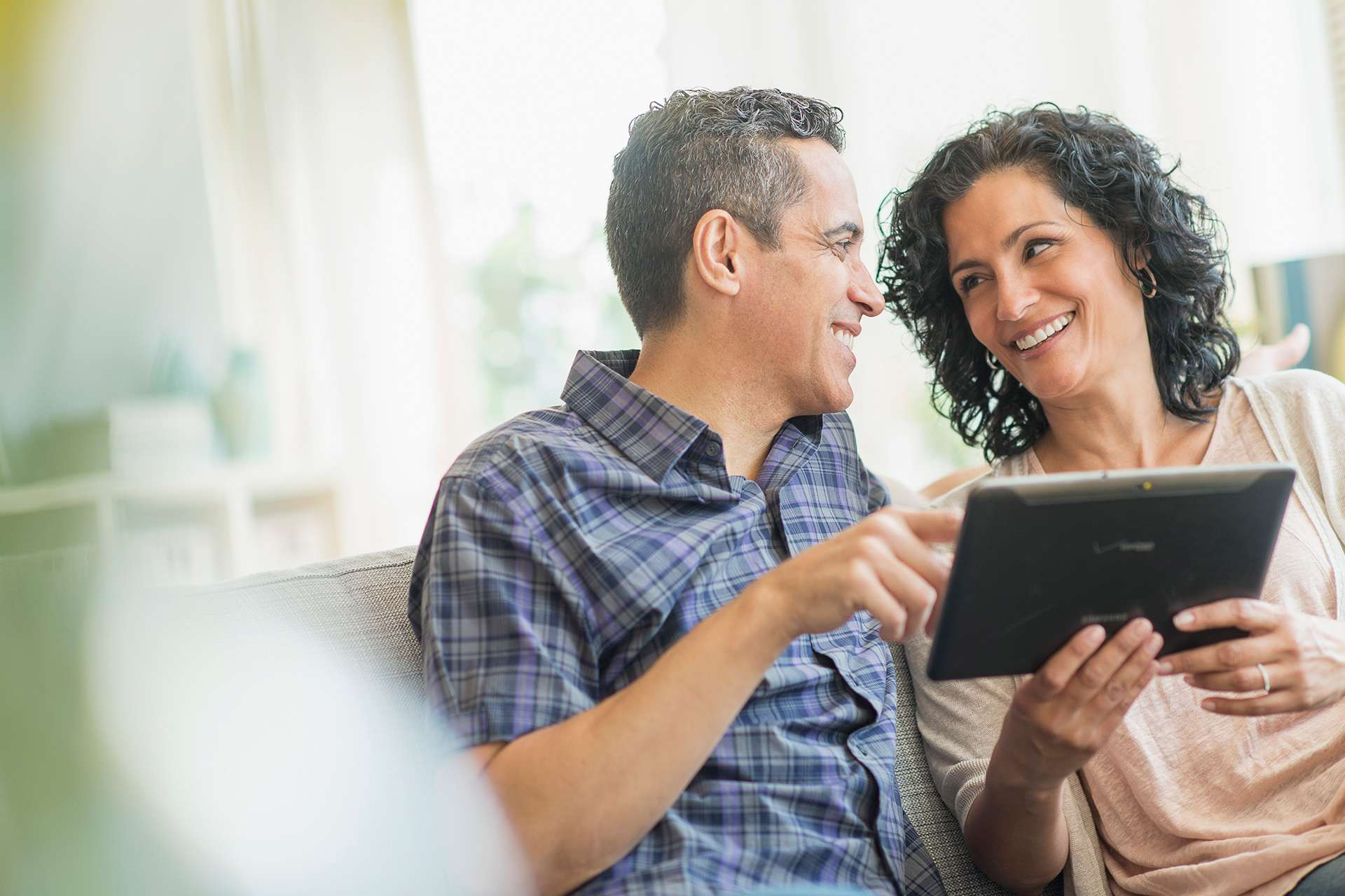 Couple on couch with tablet